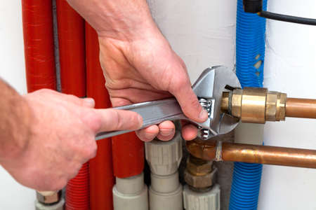 pipe wrench: Mans hands with wrench turning off valves