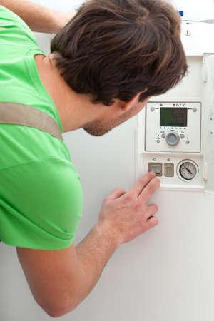maintenance fitter: Repairman in green t-shirt fixing a boiler