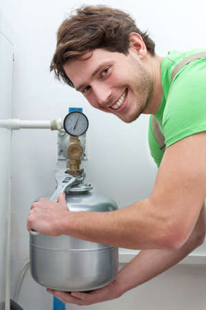 Happy man with wrench repairing a boiler photo