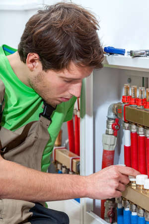 Young handsome plumber fixing the valves in boiler room Stock Photo - 24568619