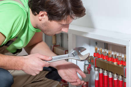 Handyman with a wrench searching a failure solution photo