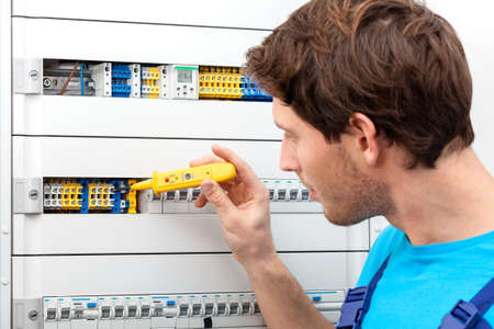 Repairman checking a voltage and fixing a switchboard photo