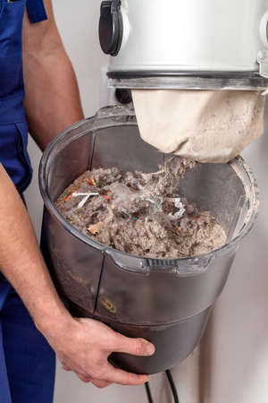 vacuum: Blue-collar hands with trash from the vacuum cleaner