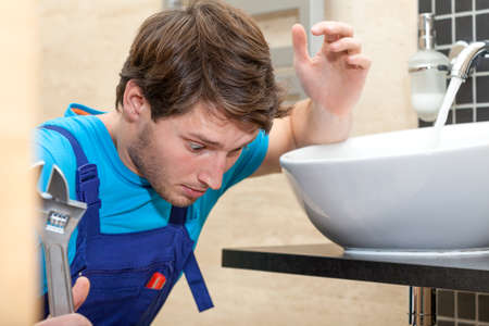 inexperienced: Young inexperienced handyman fixing the valve in bathroom