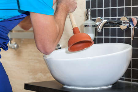 sink drain: Plumber with rubber plunger in a bathroom