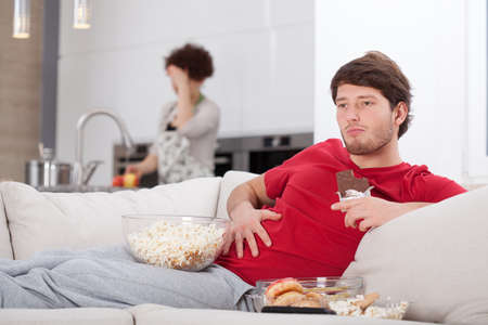 unhealthy lifestyle: Lazy guy and his hard-working wife in the kitchen