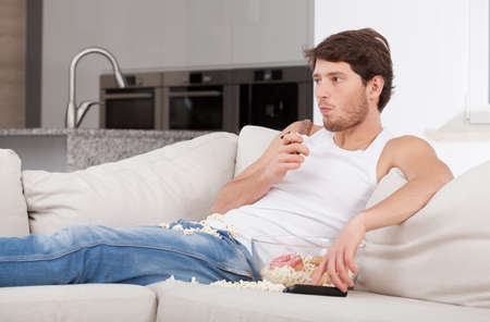 Bored man lying on couch and eating sweets Stock Photo - 24568679
