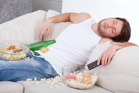 comida chatarra: Hombre completo y borracho tirado en un sof� Foto de archivo
