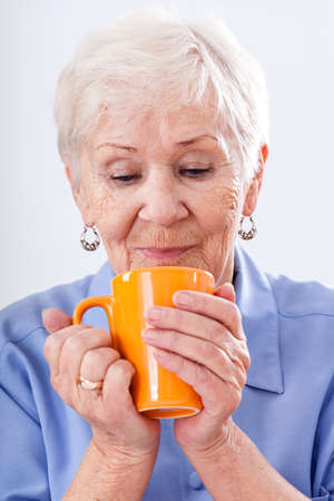 A grandma with a hot drink in an orange mug photo