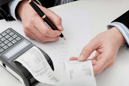 expenses: An accountant going through companys finances summing up the expenses