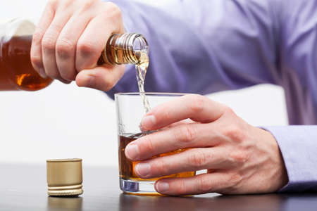 drinking problem: Businessman hands pouring alcohol into glass - alcoholism