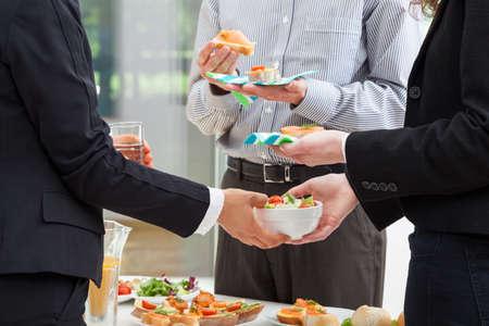 negocios comida: Los gerentes est�n desayunando en la oficina y discutir acerca de las finanzas Foto de archivo