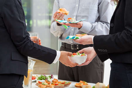 good business: Managers are eating breakfast in the office and discuss about finances  Stock Photo