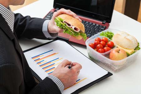 trabajador oficina: Empleado de oficina que est�n comiendo s�ndwich durante el trabajo Foto de archivo