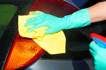 A man washing a tail light using a spray and a rag Stock Photo - 24824896