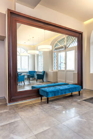 Huge mirror with wooden frame and turquoise pouf photo