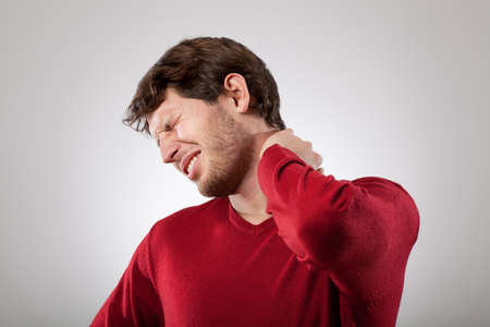 aches: Man isolated has a strong neck pain  Stock Photo
