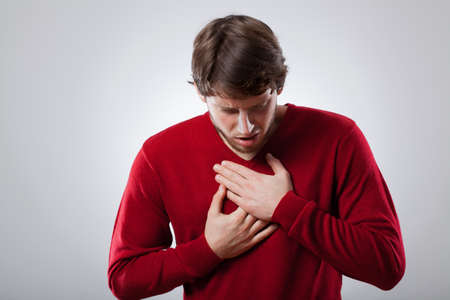 Young man with strong lungs ache holding his chest