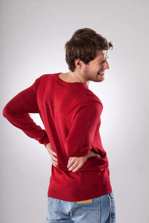 aching muscles: Young tired man suffering from strong backache Stock Photo