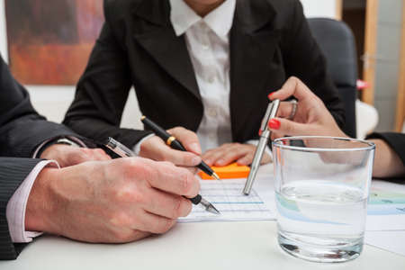 A glass of water and hands of businessmen photo