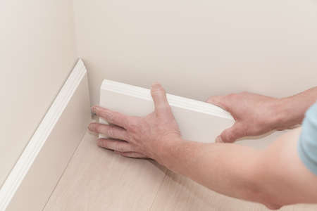 Mans hands putting white baseboard, do it yourself