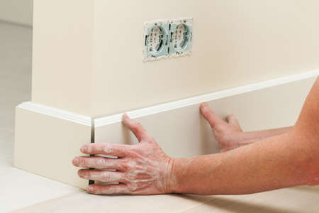 skirting: Hands fitting the baseboard to a bright wall Stock Photo