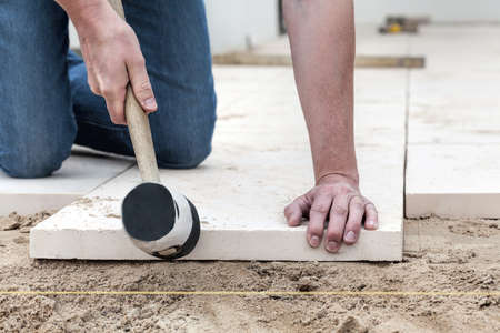 paving stone: Man hitting the concrete slab with a rubber hammer Stock Photo