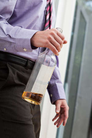 drinking problem: Drunk businessman wearing a tie, walking with the bottle in his hands Stock Photo