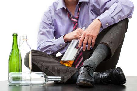 tomando alcohol: Hombre de negocios deprimido el consumo de alcohol en el suelo