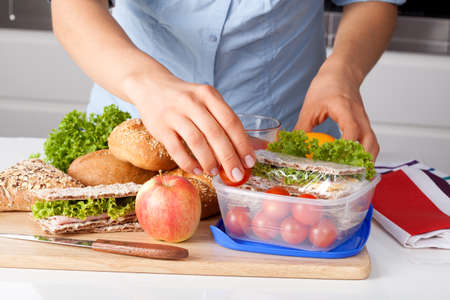 packs: Woman in blue t-shirt preparing a lunchbox in the kitchen Stock Photo