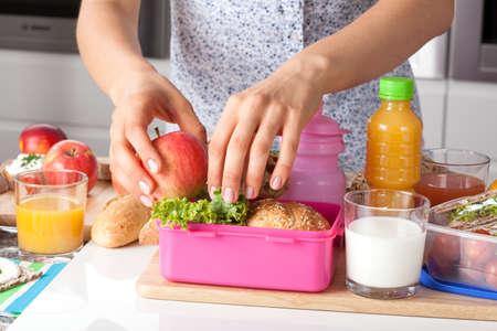 젊은 여자는 아침에 학교 급식을 만들기