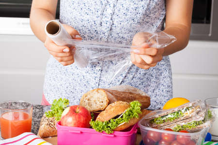 Woman packing food for lunch in plastic and boxes