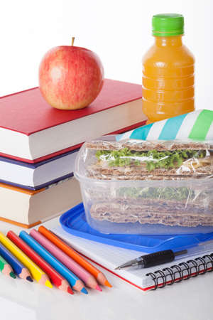 Well prepared school lunch with books and pencils on white isolated background photo