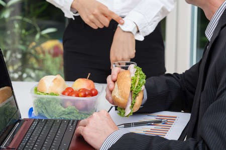 snack time: Busy worker and his angry boss pointing on a clock Stock Photo