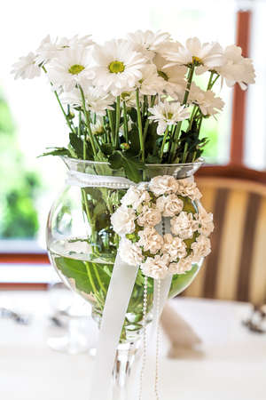 Mediterranean interior - a bunch of ox-eye daisies in a glass vase photo