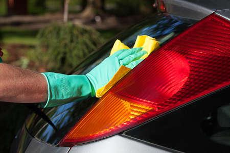 A man washing a cars back window with a rag photo
