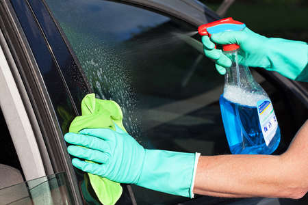 A man washing a cars window using a rag and a spray photo