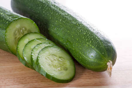 Refreshing and sliced cucumbers placed on chopping board photo