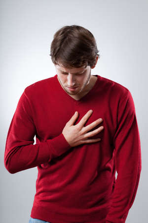 Young man has a strong lungs pain holding his chest photo