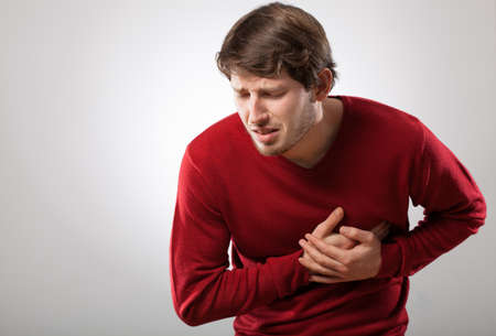 Jonge atletische man heeft een plotselinge hartaanval Stockfoto
