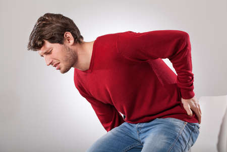 Man with strong backache cant sit on the chair photo