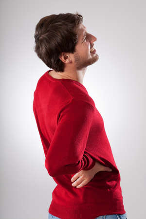 hand pain: Man isolated in red sweater suffering from strong back pain Stock Photo