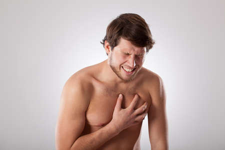 angina: Man isolated suffering from heart disease holding his chest