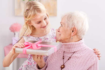 A granddaughter giving her grandma an elegantly packed gift