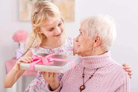 Een kleindochter die haar oma een elegant verpakt cadeau
