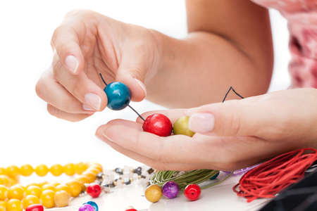 A closeup of hand stringing colorful wooden beads on a thong photo