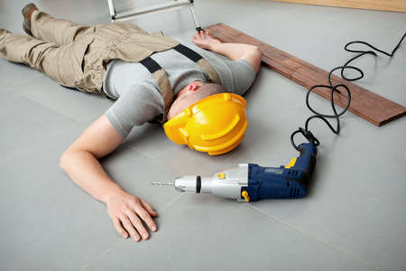 unconscious: Workman lying on the floor and injured during working Stock Photo