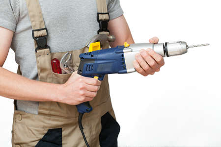 A worker in overalls holding a drill photo