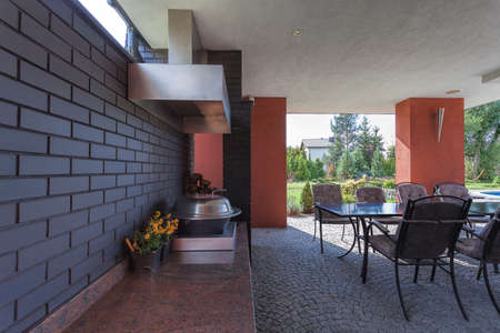 A luxurious terrace with a brickwall and garden furniture photo
