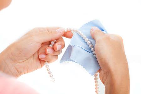 연한 파란색 티슈가있는 진주 목걸이를 연마 한 여자의 손